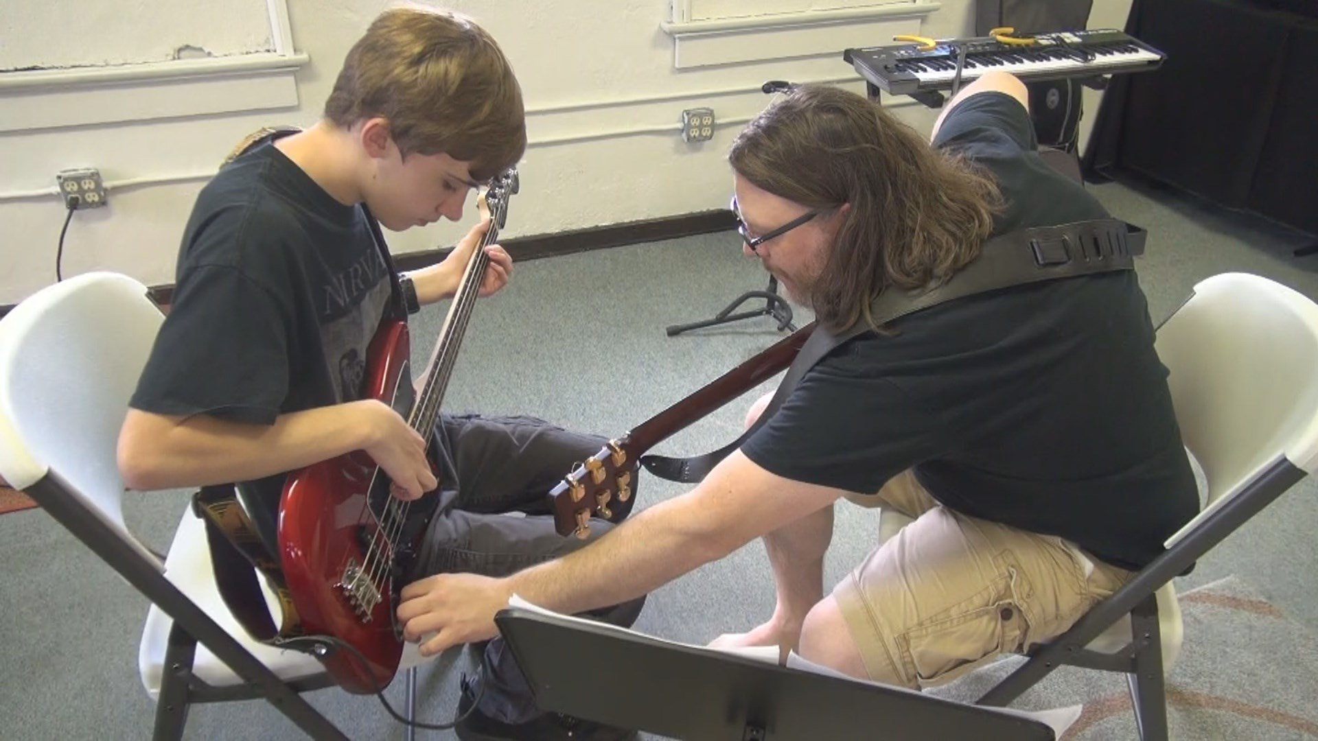 An instructor at the PopShop teaches a bassist in a one-on-one lesson.