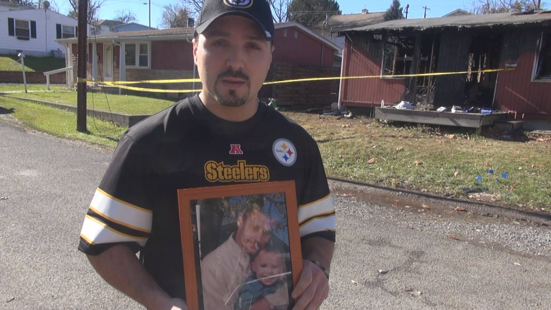Shawn Woody holds a picture of his cousin, Jimmy Smith, who died in a house fire in Westover.