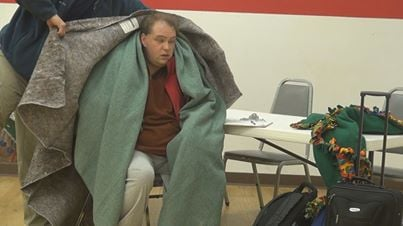 A MECCA 911 employee places a blanket on a homeless man at the Woodburn Elementary School warming shelter.