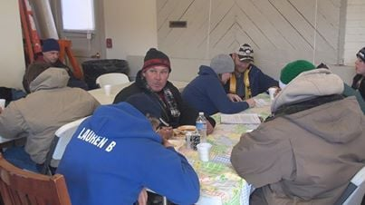 Volunteers and some of the homeless population get warm in the Morgantown Bus Depot during Registry Week.
