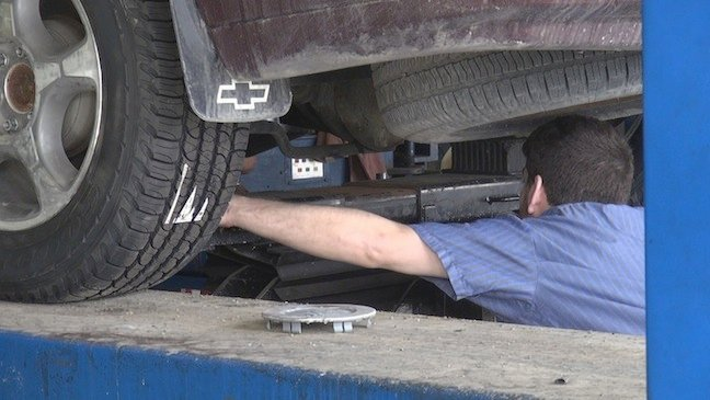 A mechanic looks under a car for damage.
