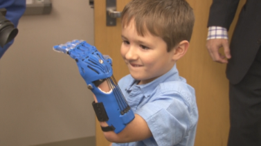 """Cooper showing off his """"cool"""" 3D printed hand."""