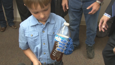 Cooper holds a water bottle with his new 3D printed hand.
